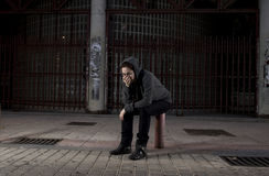 Sad woman alone on street suffering depression desperate and helpless wearing hoodie Royalty Free Stock Photo