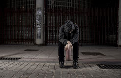 Sad woman alone on street suffering depression desperate and helpless wearing hoodie Stock Photo