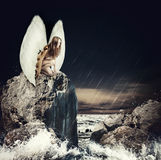 Sad woman angel with white wings. Sad woman fallen angel with white wings sitting on a rock in the sea royalty free stock images