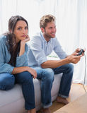 Sad woman annoyed that her partner is playing video games Stock Images