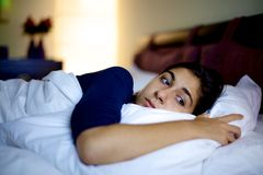 Sad woman in bed feeling lonely royalty free stock photography