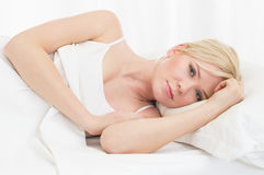 Sad woman in bed Stock Photos