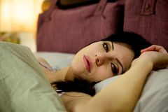 Sad woman in bed thinking Stock Photo