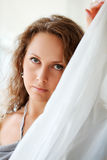 Sad woman behind a tulle Stock Image