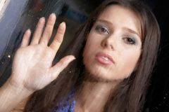 Sad woman behind wet window. Young sad woman behind wet window Royalty Free Stock Images