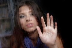 Sad woman behind wet window Stock Images