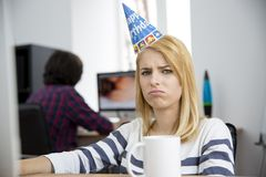 Sad woman with birthday hat sitting at the table Royalty Free Stock Images