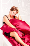 Sad woman in a black dress on a bed. Sad young woman in a black dress sitting on a bed Stock Image