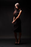 Sad woman in black dress looking down. Against dark background stock photos