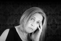 Sad woman in black and white. Black and white of woman looking sad on black damask Stock Photos