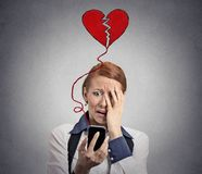 Sad woman with broken heart looking at her mobile phone. Isolated on grey wall background Royalty Free Stock Image