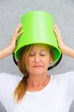 Sad woman with bucket on head Stock Image