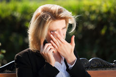 Sad business woman calling on cell phone in city park Stock Photo