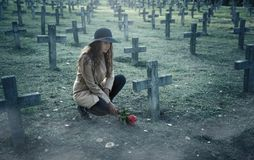 Sad woman in the cemetery . Sad woman in the cemetery, holding a bouquet of roses in her hand royalty free stock image
