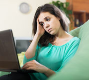 Sad woman in a chair with a laptop Royalty Free Stock Image