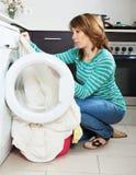 Sad woman cheking  clothes near washing machine Stock Photo