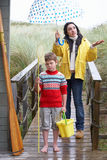 Sad woman and child with umbrella Stock Photo