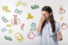 Sad woman closing her eyes after losing a favorite job. Financial situation. Unhappy young woman becoming unemployed and thinking about her financial situation Royalty Free Stock Photography