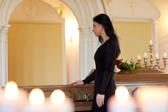 Sad woman with coffin at funeral in church. People and mourning concept - sad woman with coffin at funeral in orthodox church royalty free stock photography