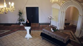 Sad woman and coffin at funeral in orthodox church stock video