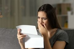 Sad woman complaining reading a letter in the night. Sitting on a couch in the living room at home Stock Photography