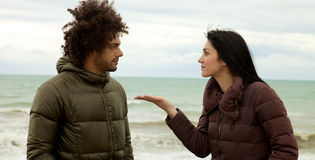 Sad woman confronting boyfriend in winter in front of ocean Royalty Free Stock Photography