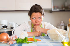 Sad woman cooking rice in the kitchen Royalty Free Stock Image