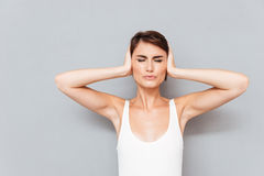 Sad woman covering her ears isolated on a gray background Stock Photography