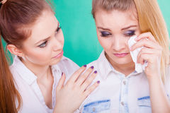 Sad woman crying and being consoled by friend. Stock Image