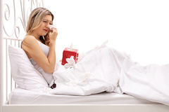 Sad woman crying and wiping her tears while lying in bed Royalty Free Stock Photography