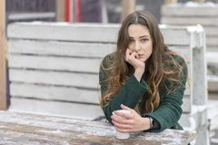 Sad woman with a cup of coffee. Leaned on a snow-covered wooden table royalty free stock photo