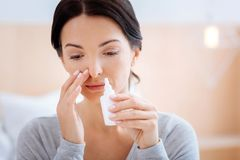 Sad woman curing her allergy with a help of nasal drops Royalty Free Stock Photos