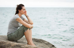 Sad woman deep in though. A sad and depressed woman sitting by the ocean deep in thought Royalty Free Stock Photo