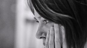 Sad Woman in Despair. A sad or anxious woman with her hand on her face Royalty Free Stock Photo
