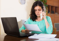 Sad woman with documents and laptop Stock Images