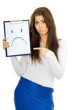 Sad woman drawing smile. Sad young woman standing expressing emotion and drawing smile on pad with blue pen Stock Images