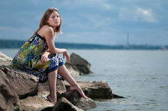 Sad woman in dress sitting on rock Stock Image