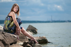 Sad woman in dress sitting on rock. Beautiful sad woman in dress sitting on rock over sea at summer storm day royalty free stock images