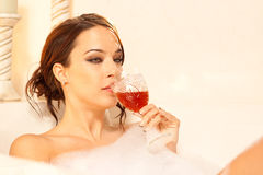 Sad woman drinking in the bath. This young lady has a lot on her mind as she takes a bubble bath Royalty Free Stock Photo