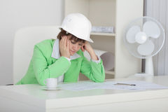 Sad woman engineer sits at table on workplac Royalty Free Stock Images