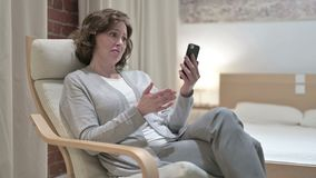 Sad Woman Facing Loss on Smartphone on Sofa