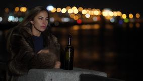 Sad woman feeling alone and depressed at night in city crying. There is a bottle of wine near her 4K Slow Mo stock footage