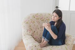 Sad woman feeling depressed looking at window. Beautiful sad woman feeling depressed looking at window at home and holding hot coffee cup sitting on living room Royalty Free Stock Photos