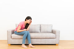 Sad woman feeling headache and physical discomfort. Sitting on couch to resting in living room wooden floor with white wall background Stock Photos