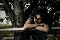 Sad woman at fence Stock Images