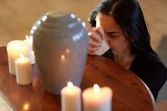 Sad woman with funerary urn praying at church Stock Photo