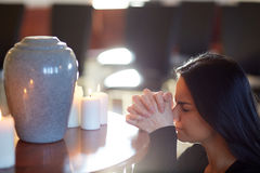 Sad woman with funerary urn praying at church Stock Photo