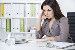 Sad woman in gray at her workplace royalty free stock image