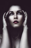 Sad woman with headache. In dark Stock Photography