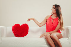 Sad woman with heart shape pillow. Valentines day. Royalty Free Stock Image